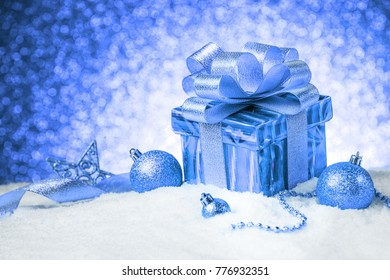 Christmas blue gift box with balls and decoration on snow