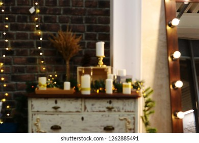Christmas blurred background decor with white candles, wooden vintage box, mirror, big light bulbs and blurred elegant christmas lights. Holiday decor with gold lightbulbs and vintage interior items.