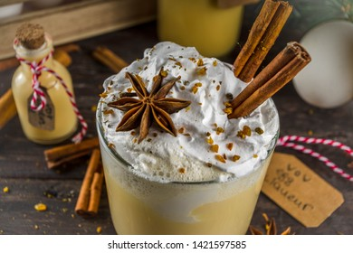 Christmas Bombardino Livigno cocktail with egg liqueur VOV and rum. With cinnamon, spices. Wooden background with christmas decorations, copy space