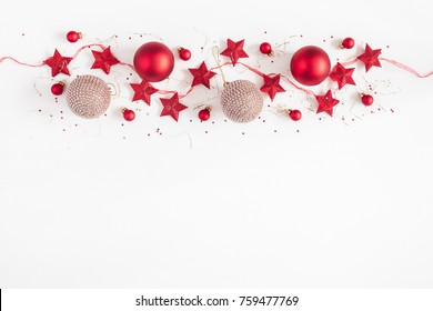 Christmas border. Christmas balls, garland, red and golden decorations on white background. Flat lay, top view, copy space