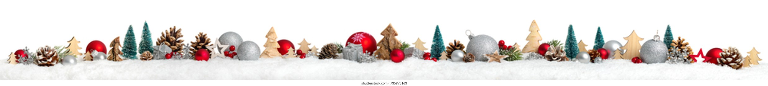 Christmas border or banner with ornaments arranged in a row on snow, extra wide and isolated on white background