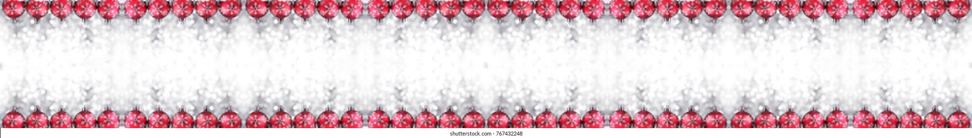 Christmas border or banner with ornaments arranged in a row on show, extra wide and isolated on white background