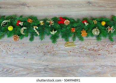 Christmas border - branches of pine with red and gold decorations and confetti, isolated on a natural wooden background, horizontal banner.