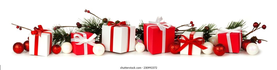 Christmas border of branches and red and white gifts over a white background