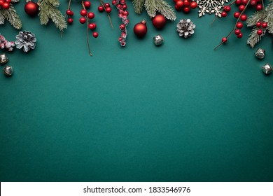 Christmas border with classic decorations. Fir branches, red balls, jingle bells on green background.