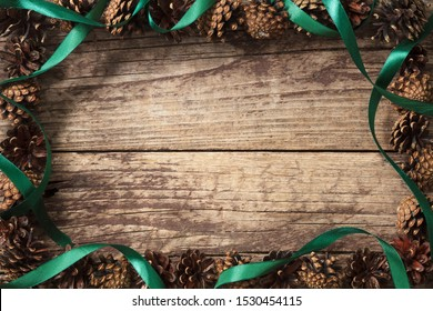 Christmas border design with green ribbon and brown pinecones on old wood background top view. Christmas pine cones border with place for text. High resolution.