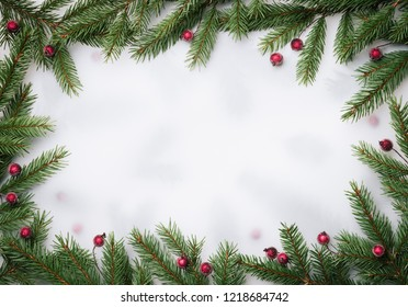 Christmas border. Frame of fir branches and holly berries. Flat lay, top view. Copy space for text. Celebration background
