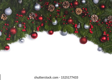 Christmas Border frame of tree branches on white background with copy space isolated, red and silver decor, berries, stars