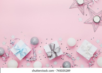 Christmas border with gift boxes, balls, decoration and sequins on pink table top view. Flat lay. Copy space for greeting card