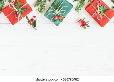 Christmas border. Christmas gifts, fir branches on wooden white background. Flat lay, top view, copy space