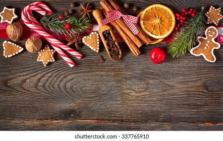 Christmas border. Gingerbread cookies, spices and decorations on wooden background.