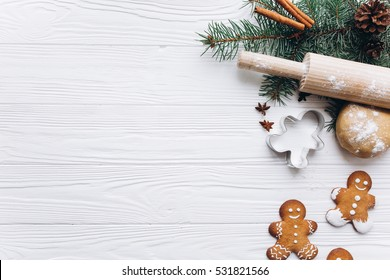 Christmas border. Gingerbread cookies, spices and decorations on white wooden background.