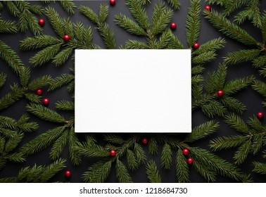 Christmas border. New Year background with copy space for text. Flat lay, top view. Decorative frame of fir branches and holly berries. Paper notice sheet