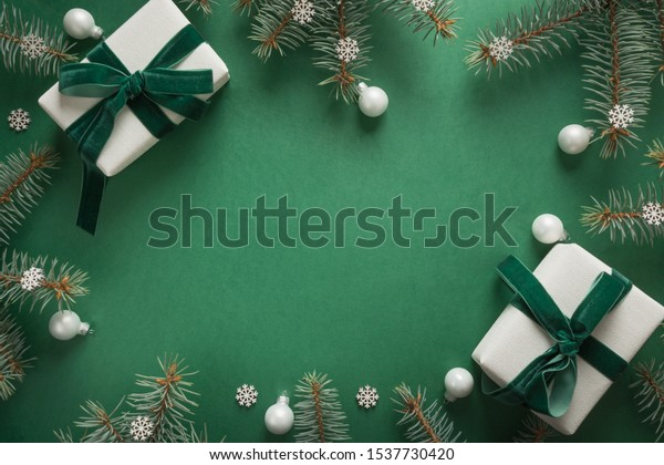 Christmas border with xmas tree and gifts on green background. Winter holiday. Happy New Year. Space for text. View from above, flat lay. Xmas. Template, mockup. Greeting card.
