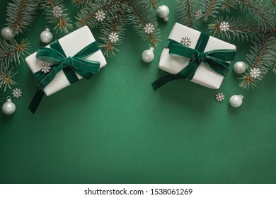 Christmas border with xmas tree and white gifts on green background. Winter holiday. Happy New Year. Space for text. View from above, flat lay. Xmas. Template, mockup. Greeting card.