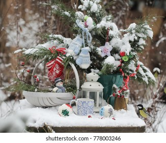 Christmas bouquet of pine branches ,knitted toys,white basket and chickadee in the snow garden