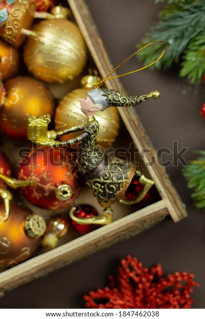 Christmas box with festive toys and decorations on dark background. Retro rustic style. Holiday, new year, xmas concept. Flat lay composition. Top view.
