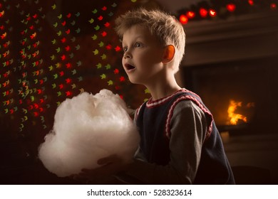Christmas boy's portrait near fireplace with candy floss in his hand