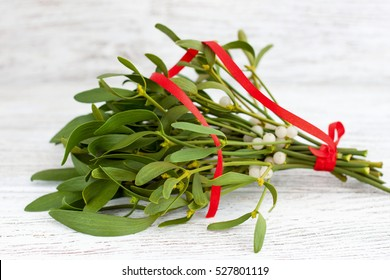 Christmas bunch of green mistletoe with white berries and red ribbon on white wooden background