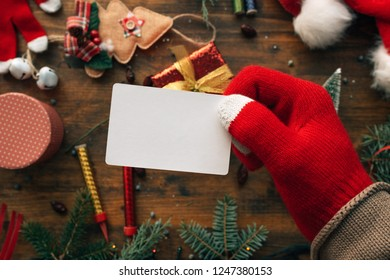 Christmas business card mock up held by the hand over table with various holiday decorations