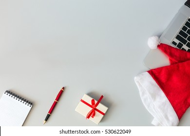 Christmas and Business Items on grey Table with Copy Space cropped Laptop Santa Cap Notepad Pen and decorated Gift Box top View flat layout