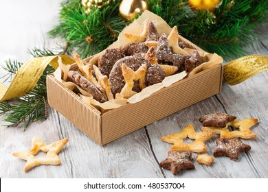 Christmas butter and chocolate cookies with festive decoration on white wooden background, selective focus. Edible gift