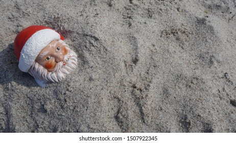Christmas by the sea. Have fun at the beach holiday with Santa Claus.  Little garden gnome in Santa Claus costume goes on vacation in the tropics and takes a sand bath (Not copyrighted)