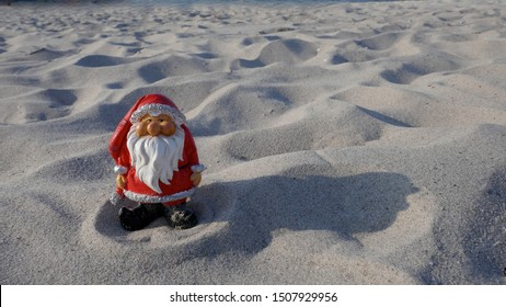 Christmas by the sea. Have fun at the beach holiday with Santa Claus.Little garden gnome in Santa Claus costume goes on vacation in the tropics.  (Not copyrighted)