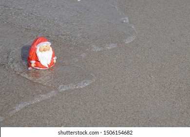 Christmas by the sea. Little garden gnome in Santa Claus costume goes on vacation in the tropics and takes a bath (Not copyrighted)