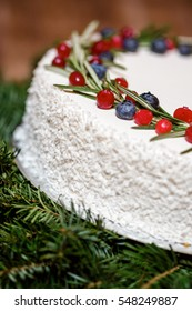 Christmas cake with cranberries and blueberries on the background of fir branches