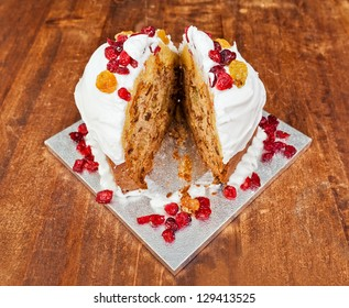 Christmas cake with cream and red berries cut in two slices