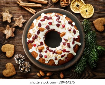Christmas cake with fruits and nuts on wooden table, top view