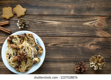 Christmas cake and gingerbread cookies on brown wooden table. Golden cones and cinnamon sticks decorations. Free space for text. Space for greeting and recipe.