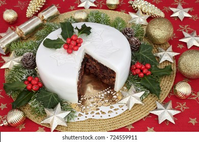 christmas cake with holly, ivy, fir, gold bauble and star decorations on red background.