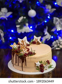 Christmas cake with winter christmas decorations, Christmas tree on the background. Chocolate vanilla cake with tangerine on top. 2021 New Year celebration.