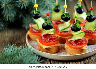 Christmas canape on skewer from bread baguette with toast cheese, sausage, tomato, cucumber and olives. Traditional snack for the New Year or Christmas party.
