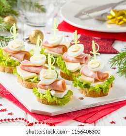 Christmas canapes on bread with brie or Camembert cheese, ham and boiled quail egg. Beautiful presentation on the festive new year's table. Delicious starter on stick
