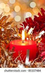 Christmas Candle burning surrounded bit golden and red ribbon