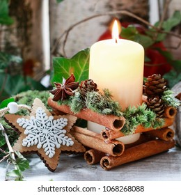Christmas candle holder with cinnamon sticks, moss and anise stars.