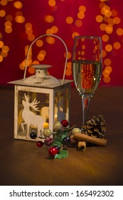 christmas candle lamp with champagne glass on wooden in front of