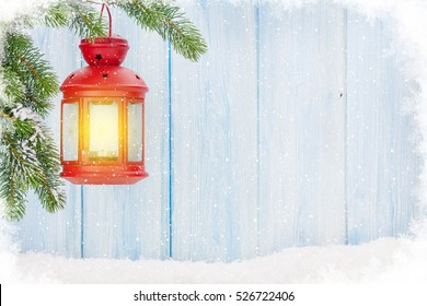 Christmas candle lantern on fir tree branch in snow. View with copy space