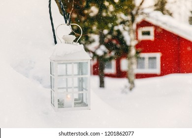 Christmas candle in lantern. Red wooden cottage in rural snowy Finland. Winter landscape.