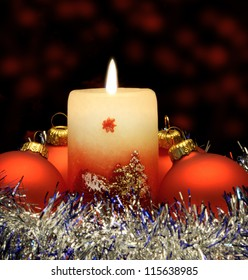 Christmas candle and red spheres. A celebratory composition