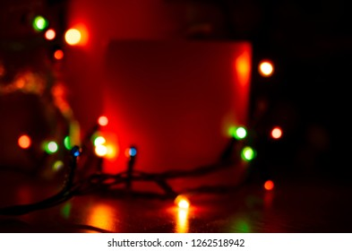Christmas candles with glowing illumination garland. New Year winter home decoration theme. For this photo applied blurring effect.