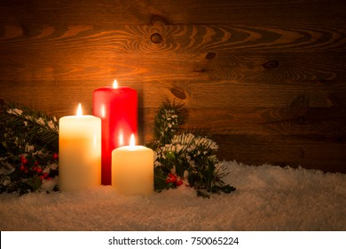 Christmas candles with Holly and conifer branches on an artificial snow and wooden background.