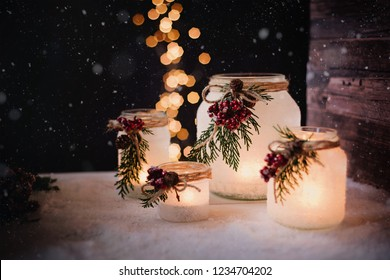 Christmas candles in jars and light bokeh in the background
