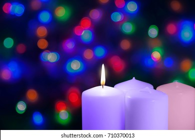 Christmas candles and lights. First Sunday of the Advent. Prophecy Candle. Decoration on a bokeh background.