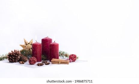 Christmas Candles on white, Weihnachtsdekoration auf weissem Hintergrund  Rote, brennende Kerzen, Zimtstangen und Zweige