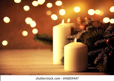 Christmas candles and ornaments over dark background with lights