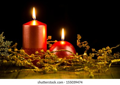 Christmas candles set against black background.